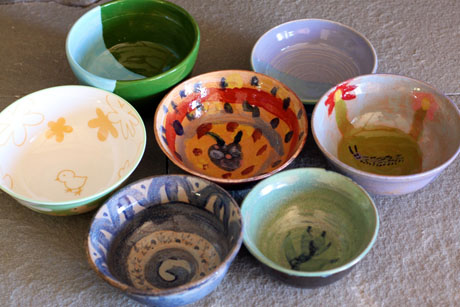Seven soup bowls decorated by kids.