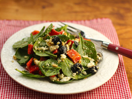 Spinach salad with pepper, olives and pine nuts, and a pesto dressing.