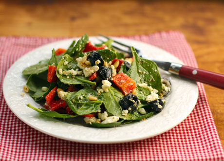 Spinach salad with bell pepper, olives, feta and pine nuts, and pesto dressing.