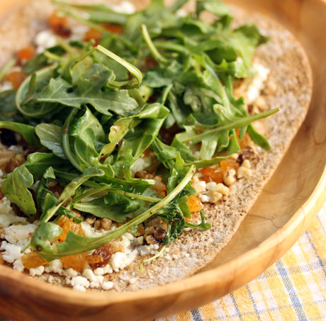 Goat cheese, raisin and walnut pizza recipe topped with fresh baby arugula leaves: like a salad, with a crust!
