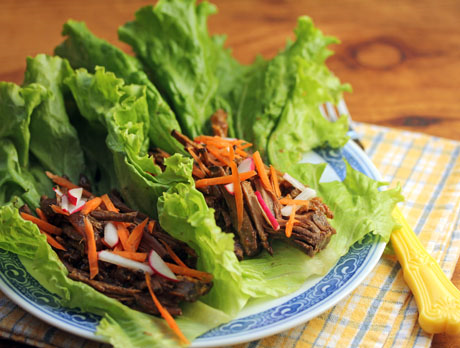 Slow cooker shredded beef wrapped in lettuce leaves: sweet and light.