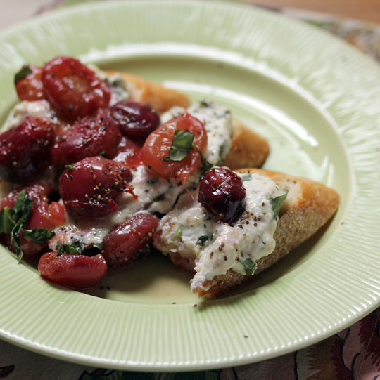 A beautiful start or end to the meal: basil ricotta bruschetta with pan-burst grapes.