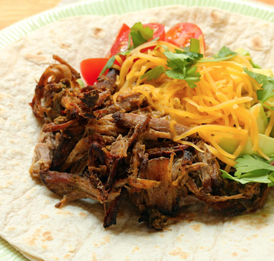 Top your own homemade beef carnitas tacos with cheese, tomatoes, and cilantro.