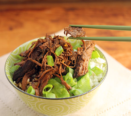Slow cooker spicy shredded beef with snow peas on a rice bowl.