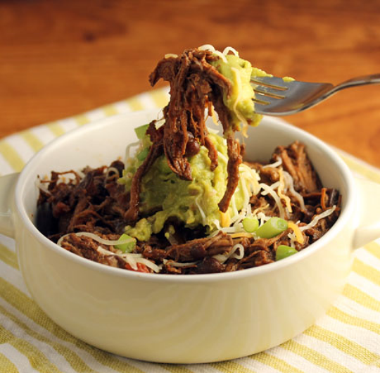 Slow cooker shredded beef chili, topped with guacamole and lime. Sublime!