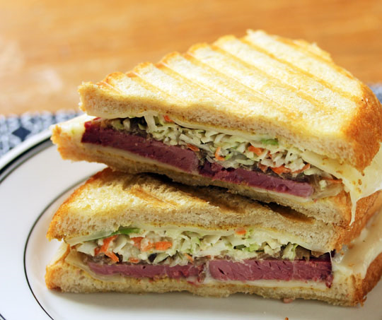 A grilled cheese sandwich filled with corned beef, caramelized onions, coleslaw, and yes, Swiss cheese. So good.