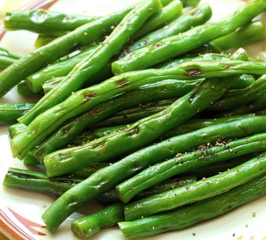 Lightly grilled green beans keep their crunch, and they're perfect for dipping in a spicy peanut-harissa sauce.