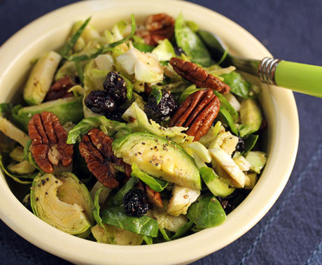 Thinly shredded Brussels sprouts with dried blueberries get tenderized by maple dressing. A quick and easy salad! #vegan #salad