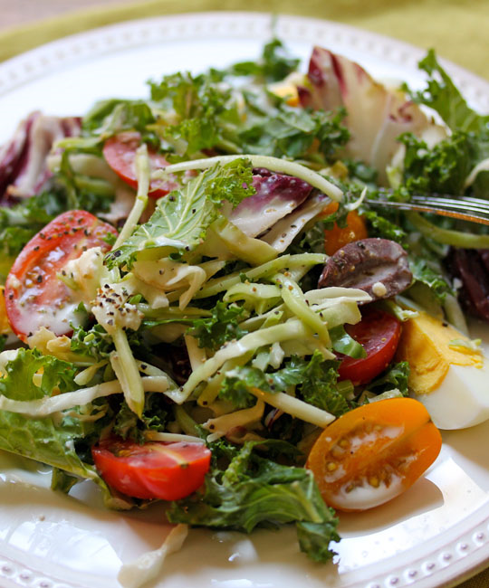 Crunchy, creamy, kale and cabbage salad, packed with mix-ins, and tossed with Greek dressing.
